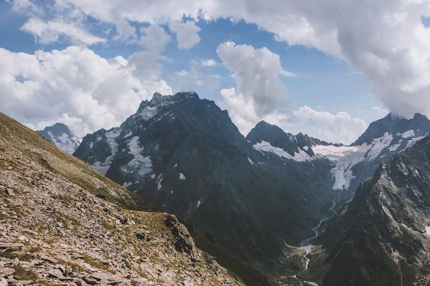 Panorama de la scène des montagnes avec un ciel bleu dramatique dans le parc national de dombay, caucase, russie. paysage d'été et journée ensoleillée
