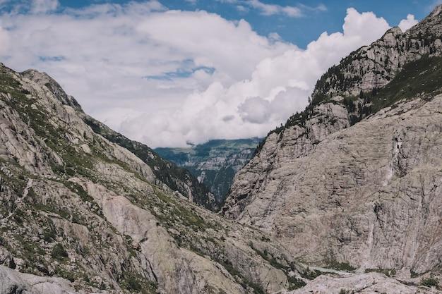 Panorama de la scène des montagnes sur la route du pont du trift dans le parc national de la suisse, de l'europe. paysage d'été, temps ensoleillé, ciel nuageux dramatique et journée ensoleillée