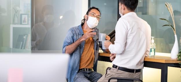 Panoramique deux employés de bureau parlant pendant la pause-café.