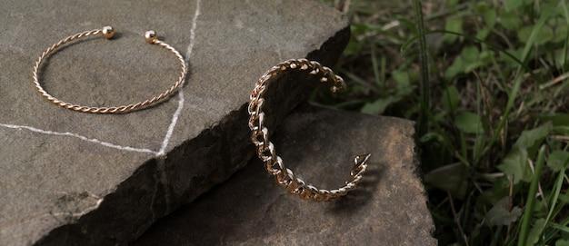 Panorma de deux bracelets en or modernes sur le rocher entre l'herbe avec espace de copie