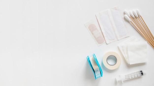 Des pansements; coton-tige; sparadrap; gaze stérile et seringue sur fond blanc