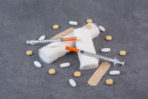 Pansements, pilules, bandages et seringues sur une surface en marbre.