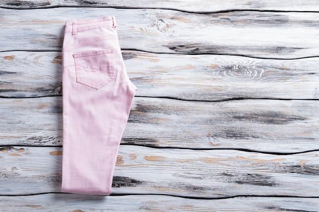 Pantalon décontracté rose clair. pantalon de dame sur fond de bois. vente saisonnière au magasin de vêtements. design simple et couleur claire.