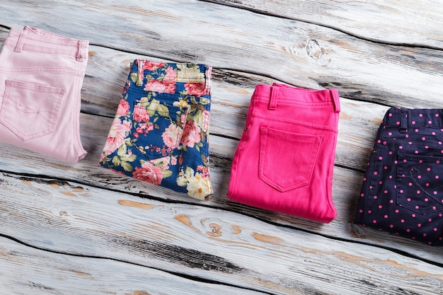 Pantalon de différentes couleurs avec motif. pantalon plié sur fond de bois. produits neufs en vitrine. toutes les tailles disponibles.