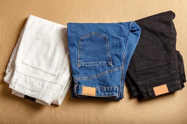 Pantalon en jean blanc bleu noir empilé. assortiment de vêtements en denim de différentes couleurs en magasin. pantalon en jean blanc, jean bleu, jean noir. vue de dessus sur table marron.
