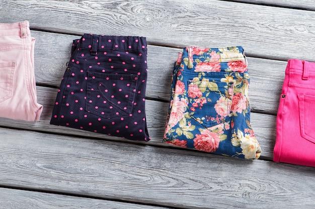 Pantalon plié sombre et lumineux. pantalon sur fond de bois gris. articles en attente de livraison. vêtements en état commercial.