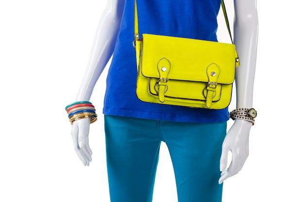 Pantalon turquoise et sac lime. porte-monnaie en cuir lime sur mannequin. nouveau sac de facteur de couleur vive. accessoires de haute qualité en magasin.