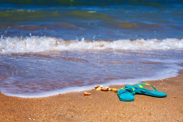 Des pantoufles bleues se tiennent sur le sable au bord de la mer.