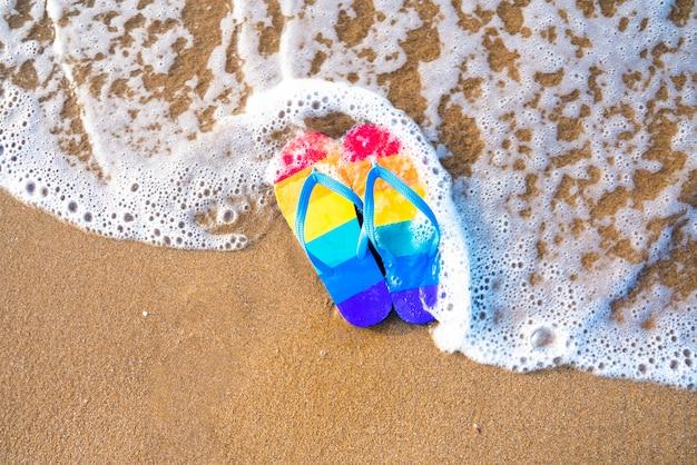 Pantoufles colorées sur la plage un jour d'été - drapeau de la fierté gaie - tongs