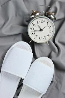 Pantoufles de couchage d'hôtel blanc et réveil sur un couvre-lit gris.