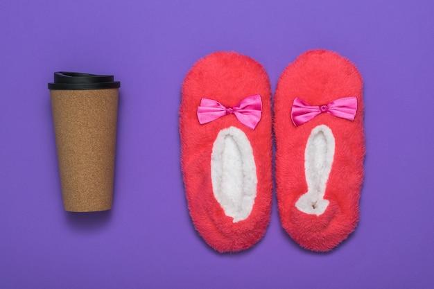 Pantoufles d'hôtel rouges et une tasse de café en papier. des accessoires pour bien commencer la journée.