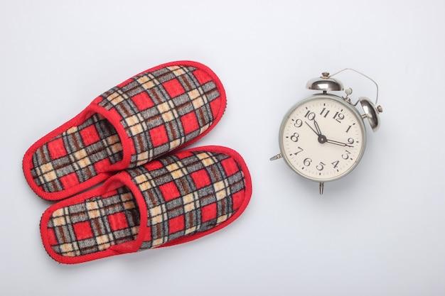 Pantoufles d'intérieur à carreaux, réveil sur fond blanc.