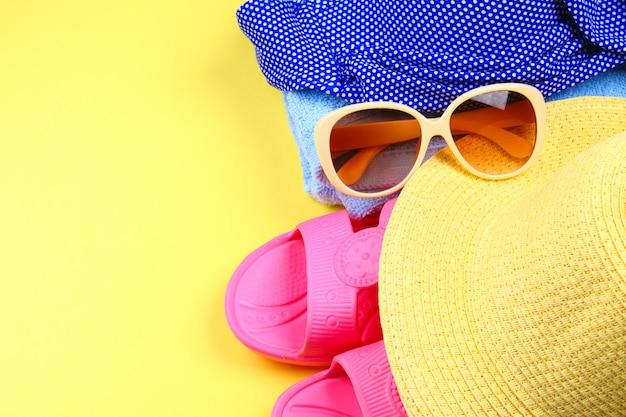 Pantoufles, maillot de bain bikini, serviette, chapeau et lunettes de soleil sur fond jaune pastel.