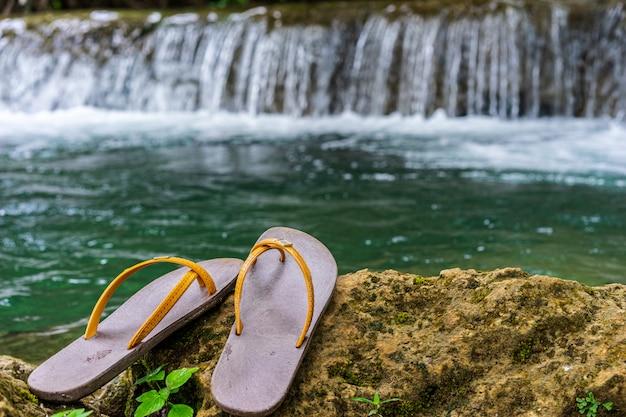 Des pantoufles ont été placées sur le rocher dans la cascade
