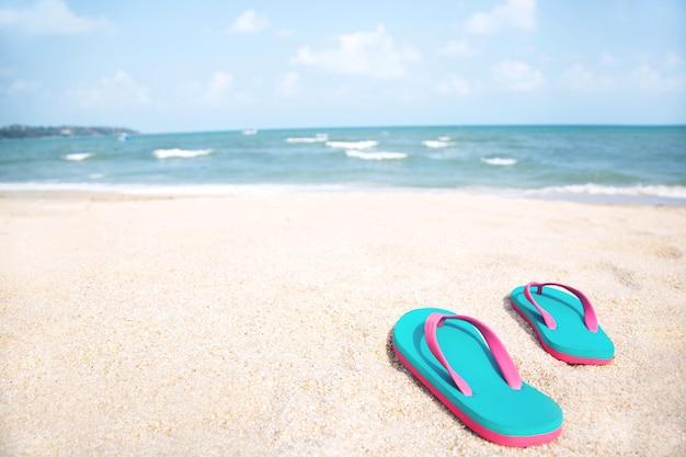Pantoufles sur la plage. distribution de l'eau des vagues de l'océan sur la plage de sable blanc.