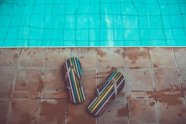 Pantoufles de plage tongs dépouillées près de la piscine sportive avec de l'eau bleue