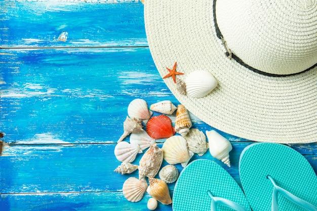 Pantoufles pour femmes - différents types de coquilles de mer plates en spirale - poisson étoile rouge - fond bleu en bois vieilli.