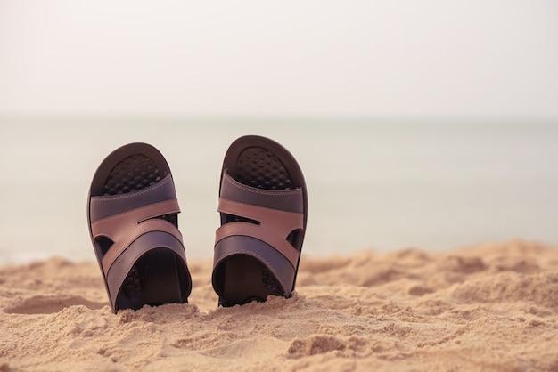 Pantoufles sur le temps de vacances sandy beach