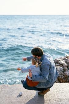 Papa accroupi tenant la petite fille sur ses genoux sur un gros rocher papa pointe son doigt vers le