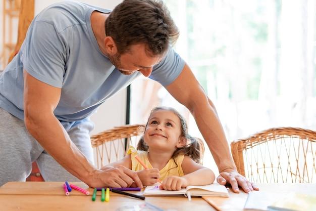 Papa admire sa fille, la regarde dessiner dans son cahier, ils font un dessin ensemble.