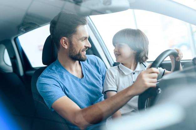 Papa apprend au petit fils à conduire de nouvelles manières.
