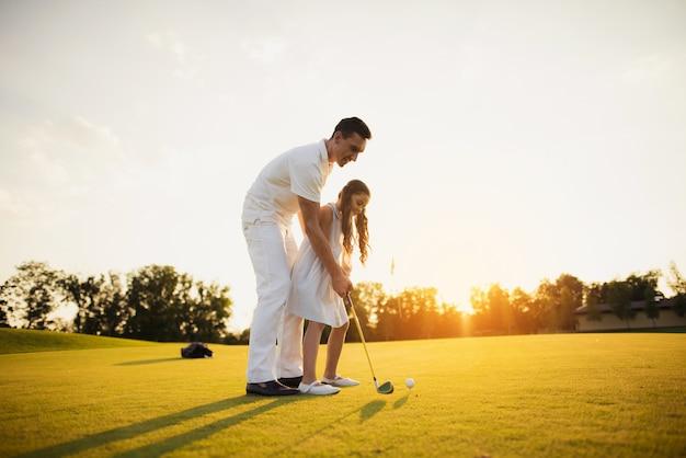 Papa apprend à un enfant à jouer au golf avec sa famille.