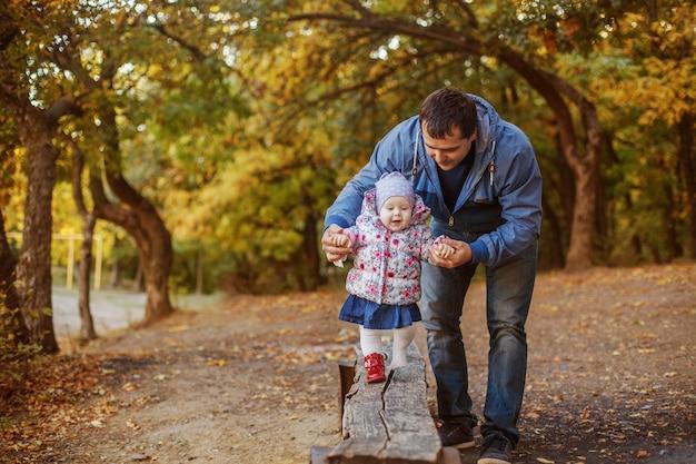 Papa apprend à sa petite fille à marcher dans le parc à l'automne