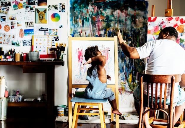 Papa artiste d'ascendance africaine donnant à son enfant un high five
