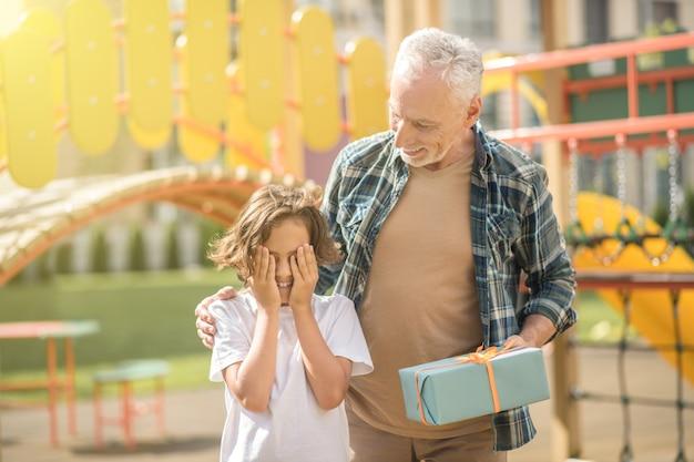 Papa aux cheveux gris donnant un cadeau à son fils excité