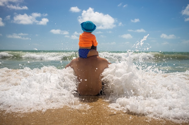 Papa avec un bébé sur ses épaules jouant dans le concept d'enfance heureuse d'écume de mer
