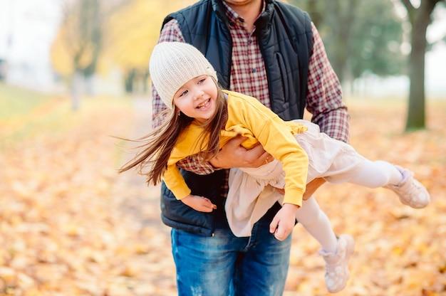 Papa en chemise à carreaux jette sa fille de cinq ans dans ses bras dans un parc en automne