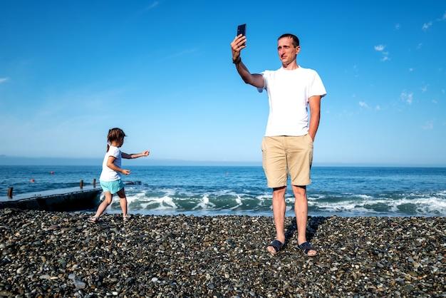 Papa communique via une communication vidéo en ligne avec sa famille. concept de blogueur de vacances communes avec un enfant. fête des pères.