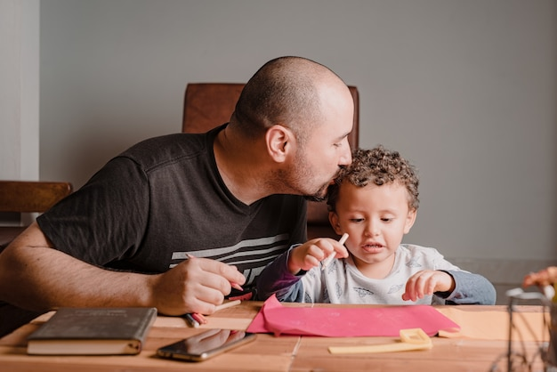 Papa embrasse avec amour son fils sur la tête pendant qu'il fait ses devoirs
