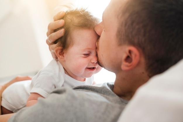Papa embrasse bébé au front