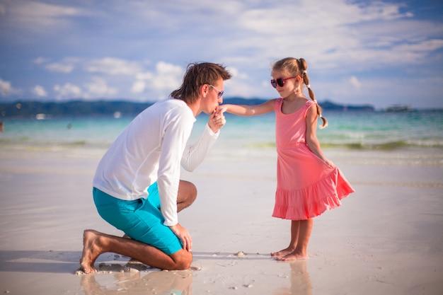 Papa embrasse la main de sa petite fille sur une plage exotique