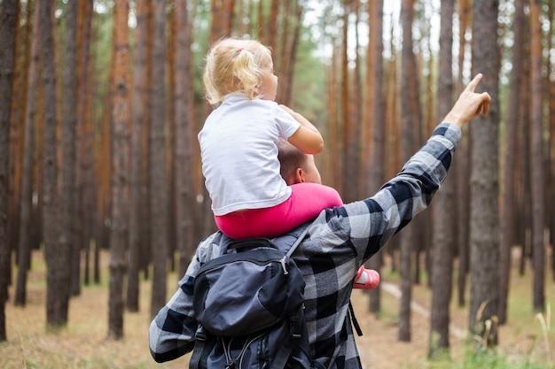 Papa avec un enfant lors d'une randonnée en forêt. randonnée familiale en montagne ou en forêt.