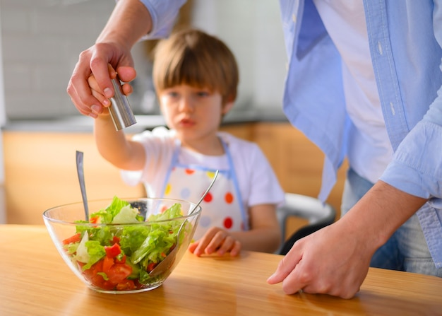 Papa et enfant mettent du sel dans la salade