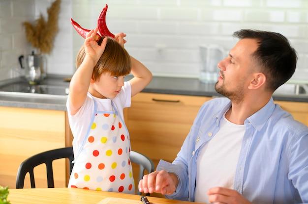 Papa et enfant s'amusant avec des poivrons kapia