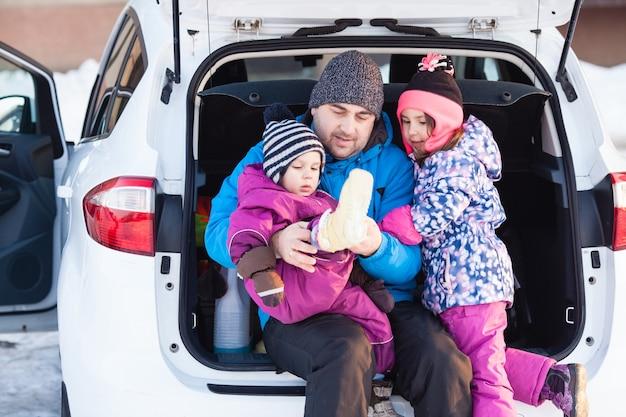 Papa avec des enfants assis dans le coffre de la voiture et se préparant pour le ski
