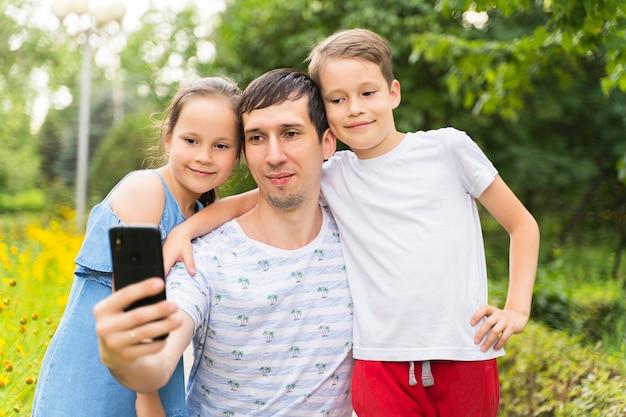 Papa et enfants heureux prennent des selfies.