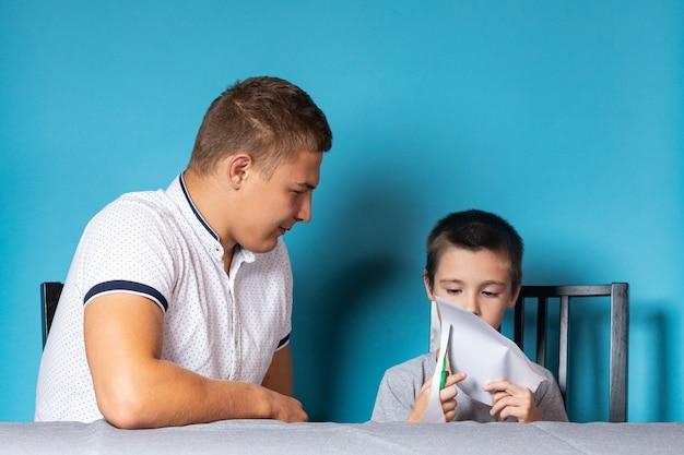 Papa enseigne à l'enfant à la maison, l'enseignement à domicile. père aide son fils à faire ses devoirs, papier découpé
