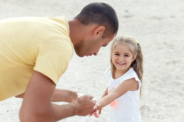 Papa essuie les mains de son enfant avec une serviette sur la plage