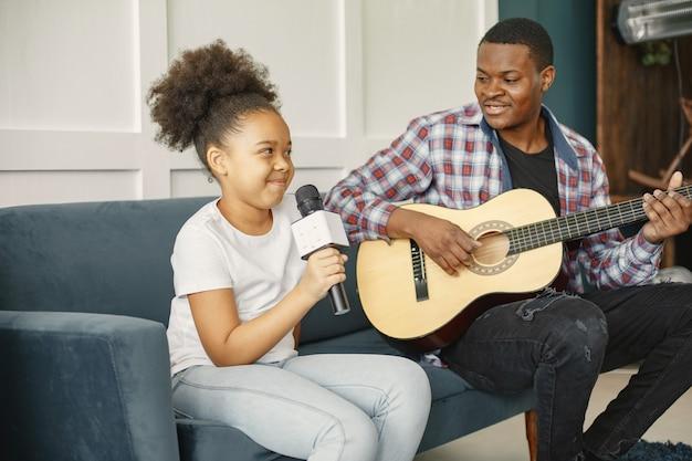Papa est assis avec une guitare et sa fille avec un microphone