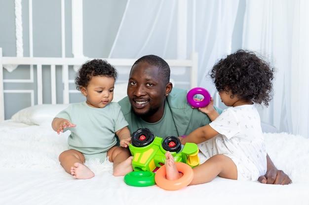Papa de famille afro-américain avec des bébés enfants joue et collectionne une pyramide colorée à la maison sur le lit, famille heureuse
