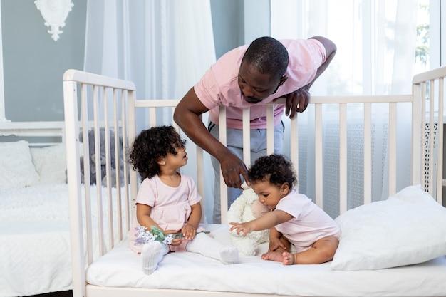 Papa de famille afro-américain avec des enfants bébés dans la chambre à la maison, papa met les enfants au lit