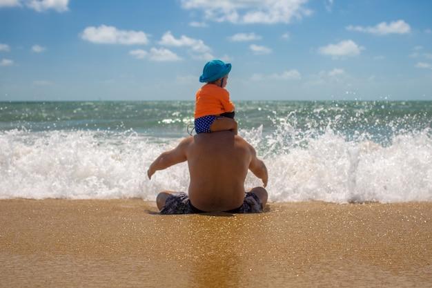 Papa fête des pères avec un bébé sur ses épaules jouant dans les embruns d'écume de mer enfance heureuse