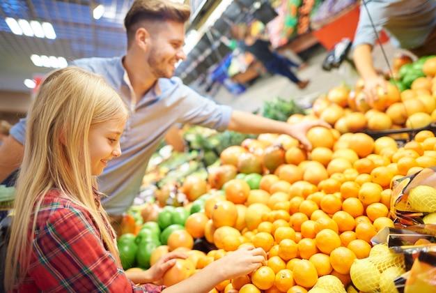 Papa et fille comparant des fruits