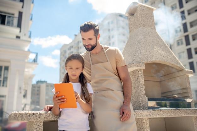 Papa et fille regardant quelque chose sur une tablette