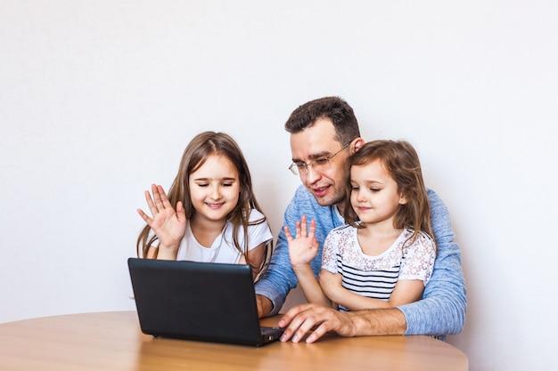 Papa et filles communiquent via internet avec leurs proches