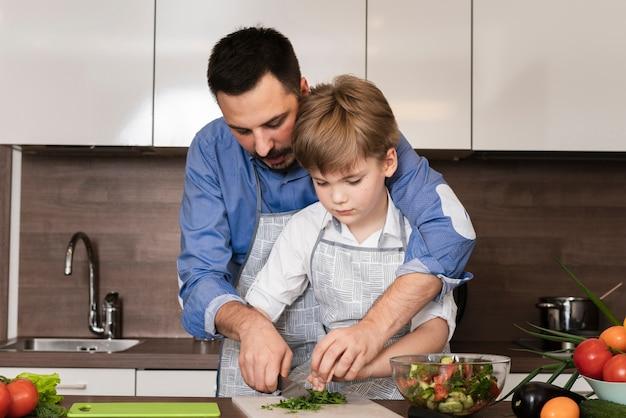 Papa et fils coupant des légumes